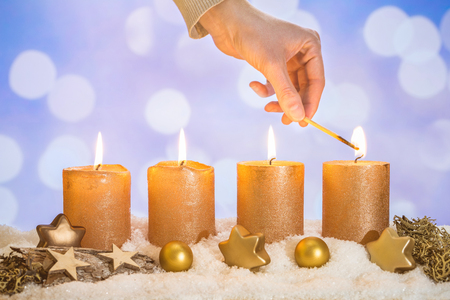 Four gold advent candles with four candles lit by hand with match and christmas decoration lying in snow as template