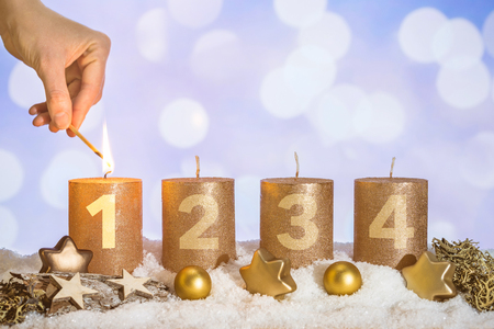 Four numbered gold advent candles with first candle lit by hand with match and christmas decoration lying in snow as template 写真素材