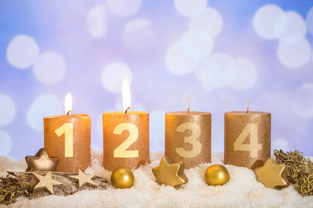 Four numbered gold advent candles with two candles lit and christmas decoration lying in snow as template