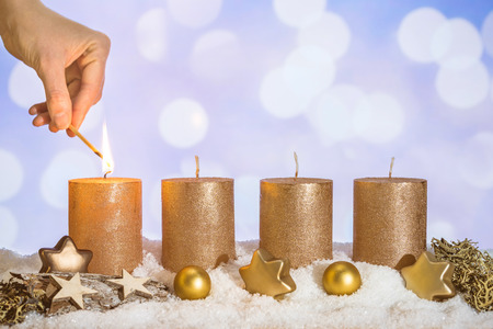 Four gold advent candles with first candle lit by hand with match and christmas decoration lying in snow as template