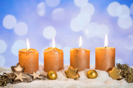 Four golden advent candles with four candles lit and christmas decoration lying in snow as template Imagens