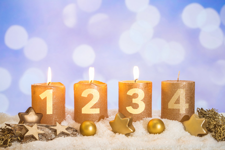 Four numbered gold advent candles with three candles lit and christmas decoration lying in snow as template
