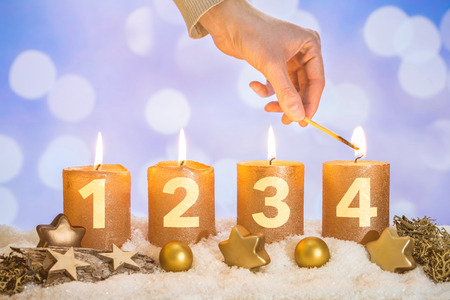 Four numbered gold advent candles with four candles lit by hand with match and christmas decoration lying in snow as template