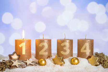 Four numbered gold advent candles with first candle lit and christmas decoration lying in snow as template Imagens