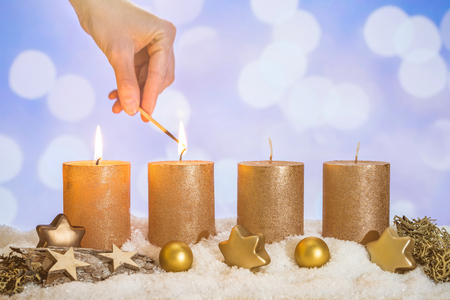 Four gold advent candles with two candles lit by hand with match and christmas decoration lying in snow as template