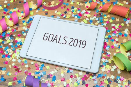 Colorful confetti and paper streamers on wooden table in background with white tablet and goals 2019 message written on display Imagens