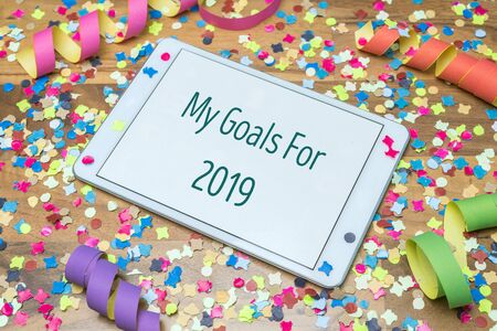 Colorful confetti and paper streamers on wooden table in background with white tablet and my goals for 2019 message written on display Zdjęcie Seryjne