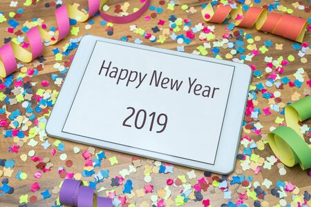 Colorful confetti and paper streamers on wooden table in background with white tablet and happy new year 2019 message written on display Imagens