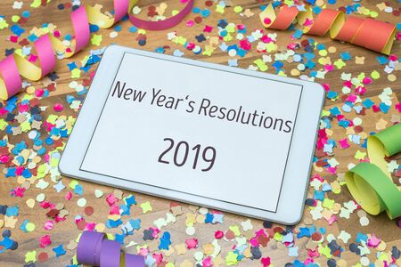 Colorful confetti and paper streamers on wooden table in background with white tablet and New Years Resolutions 2019 message written on display
