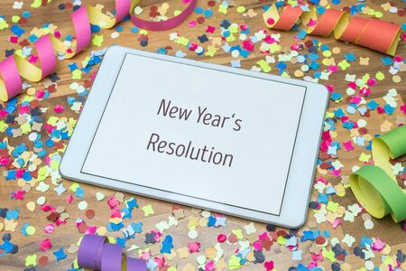 Colorful confetti and paper streamers on wooden table in background with white tablet and new years resolution message written on display Imagens