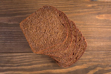 Sliced black rye bread on wooden background Stock Photo