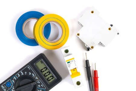 Electrical modular circuit breaker, insulating tape and digital multimeter. Electrical network protection and switching. Stock Photo