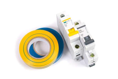 Disyuntor eléctrico modular y cinta aislante. Protección y conmutación de redes eléctricas. Foto de archivo