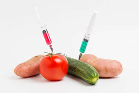 Vegetables and syringe with nitrates. GMO food ingredient.