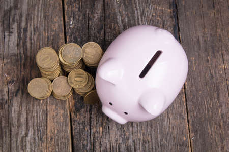 piggy bank with coin on wooden table Stock Photo
