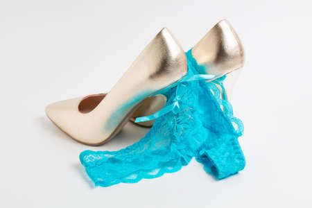 womens high-heeled shoes and panties on white background