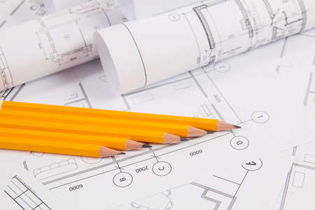 Pencils and paper engineering drawings and blueprints. Фото со стока