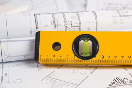 spirit level and paper drawings and blueprints.