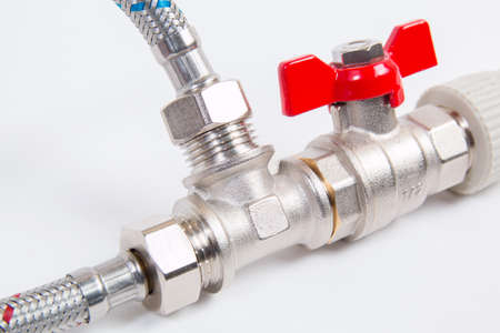 Plumbing gate ball vales, flexible water hose and fittings on a white background