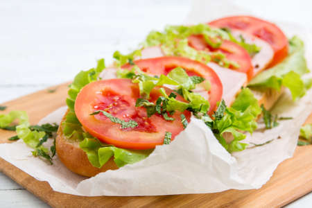 baguette sandwich with ham, tomatoes and lettuc Stock Photo
