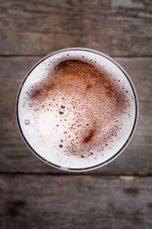 Beer in glass. Beer foam. View from above on dark wooden table