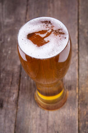 lager draft beer in a glass on dark wooden table