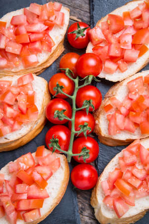 Traditional Italian bruschettas with cherry tomatoes on stone plate Foto de archivo - 125584518