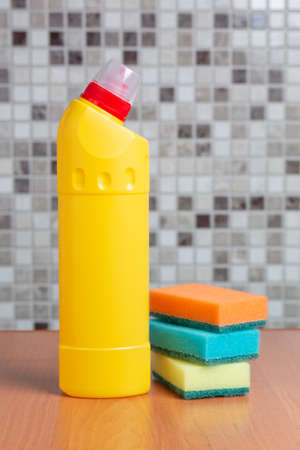 plastic bottle with cleaning agent and sponges on the table Foto de archivo