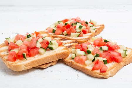 Italian bruschettas with sliced tomato cucumbeand vegetables. Foto de archivo