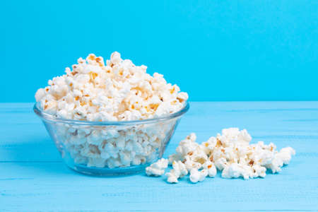 popcorn in a glass bowl on a blue table