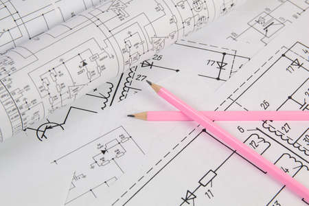 Work of an electronic engineer. Electrical engineering drawings and pencils.