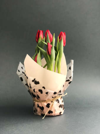 Red tulips in a vase on grey background Stock Photo