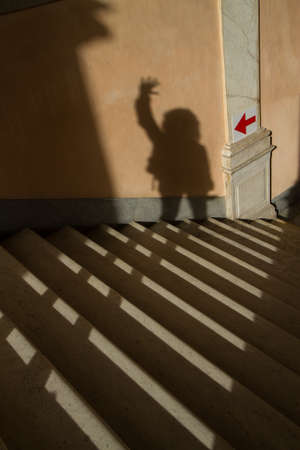 stairwell: Shadow of a person with hand in the air going in stairwell pointed by an arrow