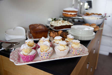 Homemade cakes and buns on sideboard