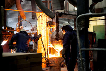 crucible: Steel workers, pourning moulten metal from crucible