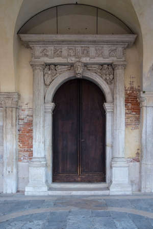 panelled: Wooden door in arched stone surround