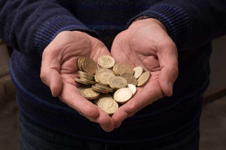 pounds: The love of money, hands holding UK pounds coins