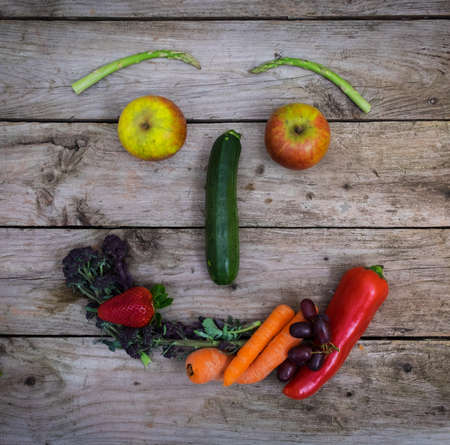 Healthy diets means happy life, fruit and vegetables arranged in the shape of a face. Stock Photo