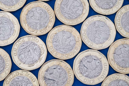 UK money, pound coins on blue background