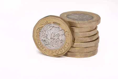 Stack of british sterling pound coins on white background Imagens