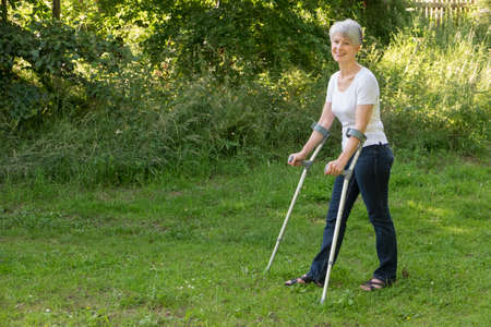 Senior grey haired woman walking with crutches