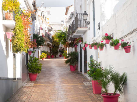Pretty cobbled street in Estepona, Spain, with cute pink plantpots for container gardening Stock Photo