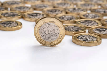 UK money, pound coin standing on edge with other coins in background Stock Photo