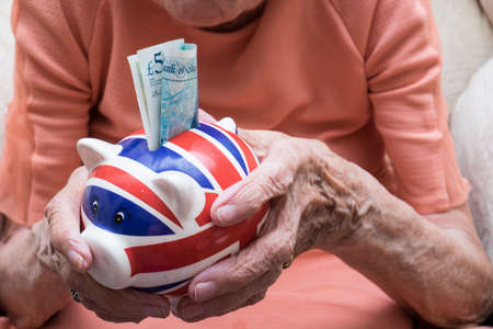 Pensioner holding out savings, union jack piggy bank