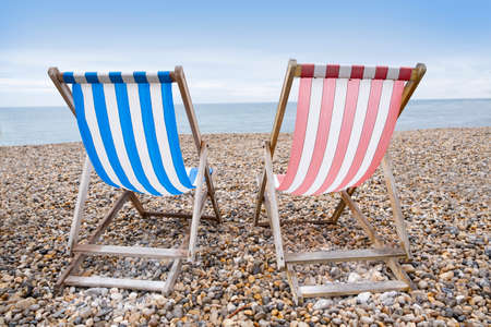 Deckchairs on beach, typical english seaside holiday scene, red and blue stripes representing main political party of labour or conservative