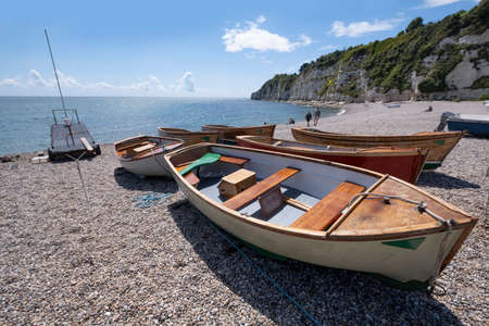 Wooden boats washed up on shingle beach at Beer, South Devon, UK. Stock Photo