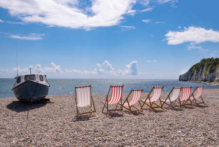 Dechairs and boaton shingle beach at Beer, Devon, United Kingdom Stock Photo
