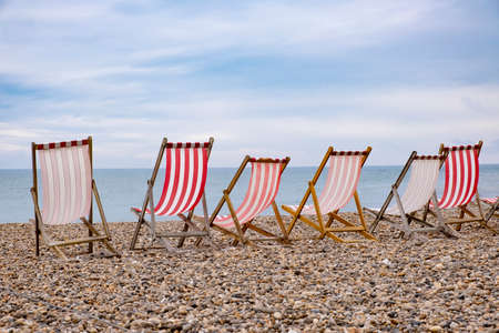Deckchairs on beach, typical english seaside holiday scene, red and white stripes Stock Photo