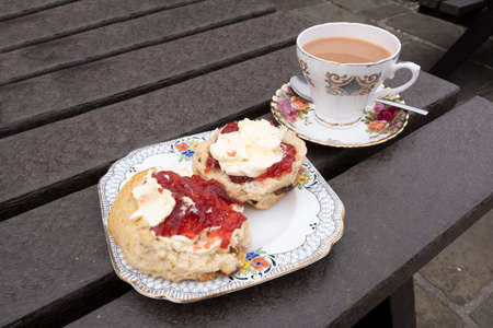 Scone with jam and cream, one half with cream first, the other with jam first, with a cup of tea in vintage china Stock Photo