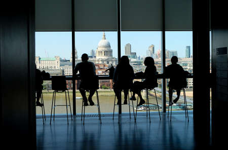 City of London, United Kingdom 6th July 2019: London skyline including St pauls cathedral, view seen from cafe at Tate on south bank, river Thames in foreground, silhouettes of people on chairs enjoying view